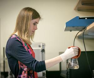 Sam, undergraduate researcher, at work in biochemistry lab