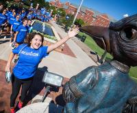Student reaches to touch beak of Billy's statue